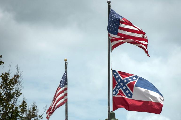 Le drapeau du Mississippi, en dessous du drapeau américain, comportait l'emblème confédéré jusqu'à la loi du 30 juin 2020