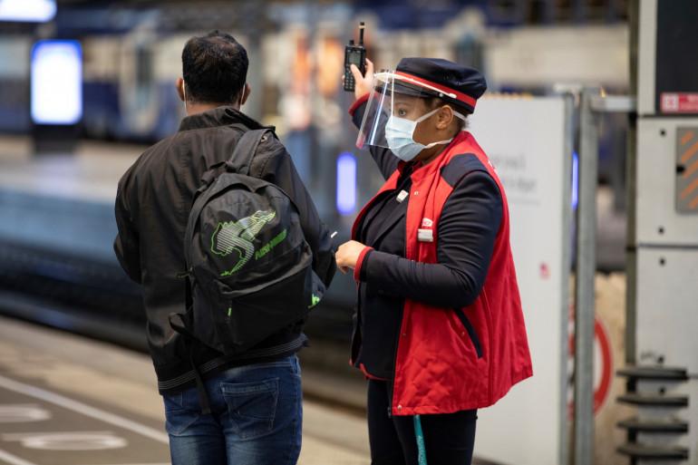 Une femme agent SNCF, portant un masque, et indiquant le chemin à un voyageur. (illustration)