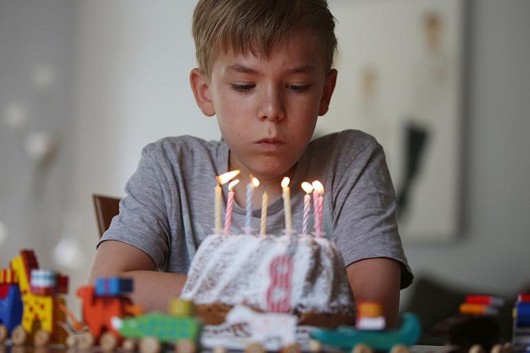 Un enfant souffle les bougies qui ornent son gâteau d'anniversaire (Illustration)