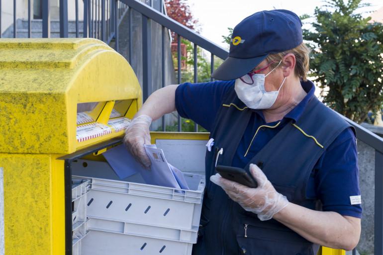 Une factrice portant masque et gants de protection. (Illustration)