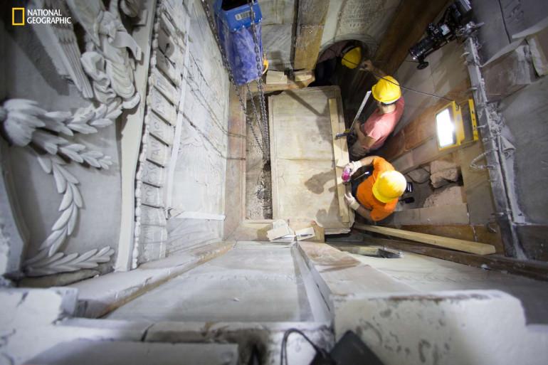 Des ouvriers soulèvent la dalle de marbre du tombeau de Jésus à Jérusalem.