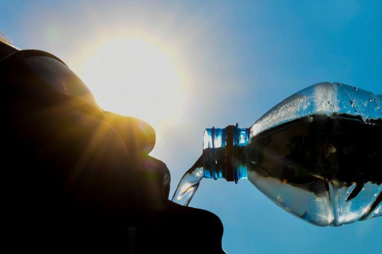 Un homme boit de l'eau sous un soleil de plomb (illustration)