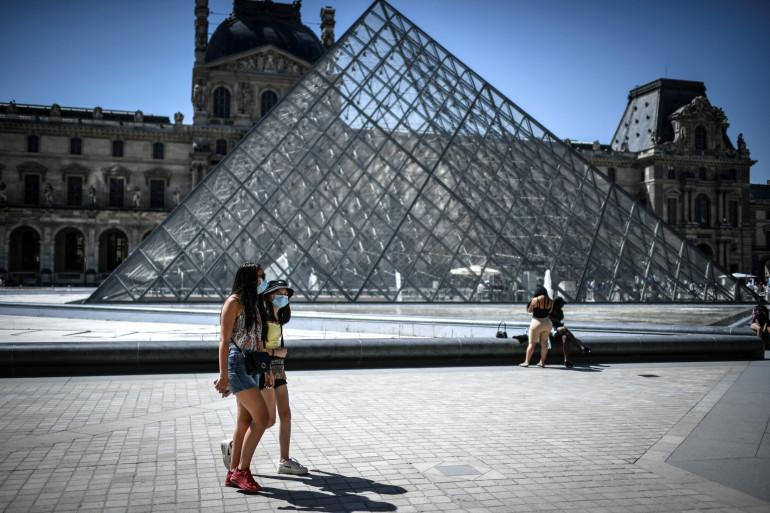 Des personnes portant le masque devant le musée du Louvre à Paris (illustration).