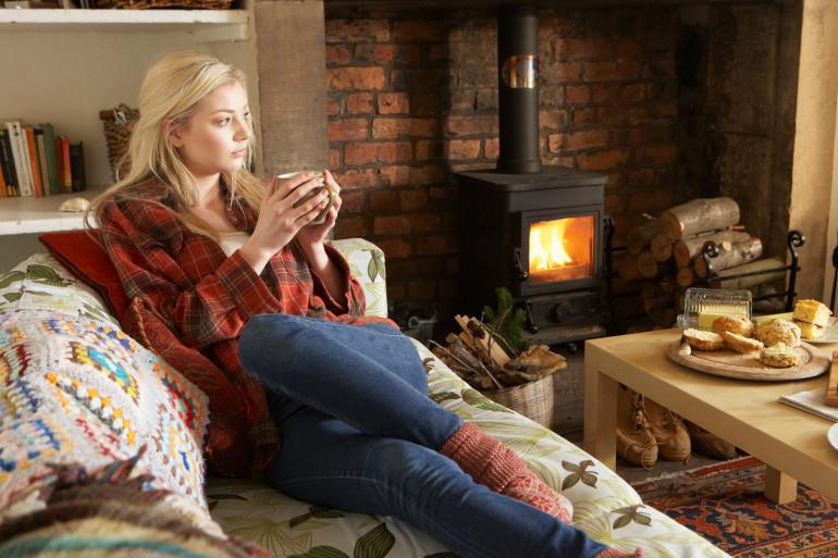 Hiver : une jeune femme se réchauffe en buvant une boisson chaude