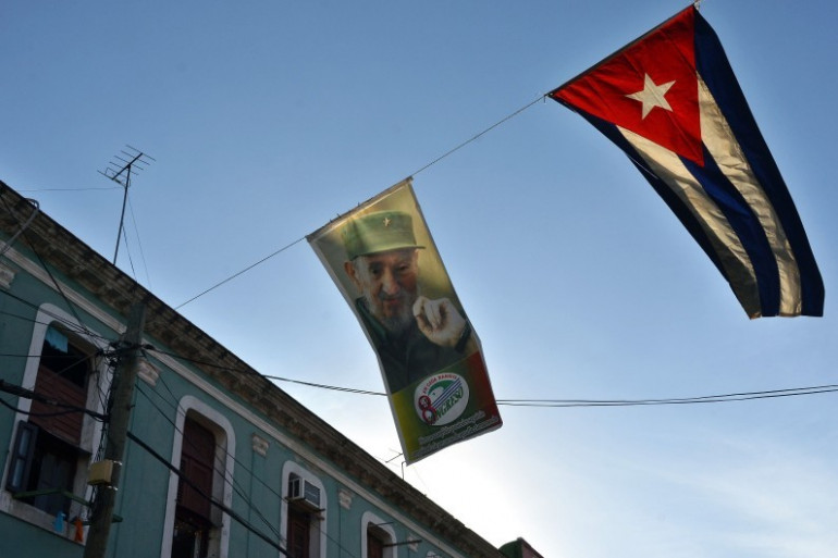 Un drapeau de Cuba et un autre représentant Fidel Castro à La Havane