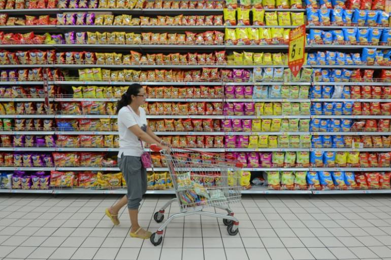 Une femme dans les rayons d'un supermarché (illustration)