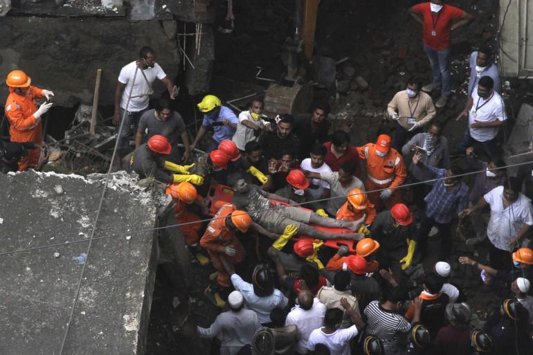 Les équipes de secours évacuent un survivant dans l'immeuble résidentiel de trois étages qui s'est effondré à Bhiwandi.