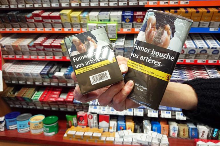 Un buraliste présente des paquets de cigarettes neutres