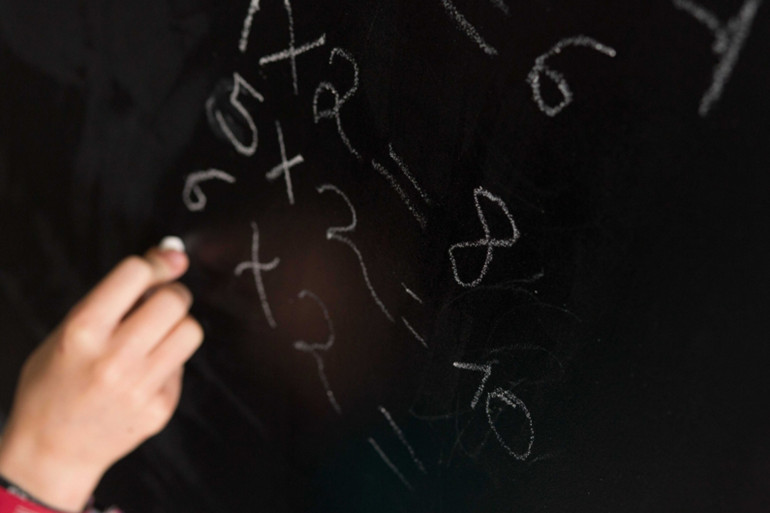 Une élève résout un problème de mathématiques au tableau