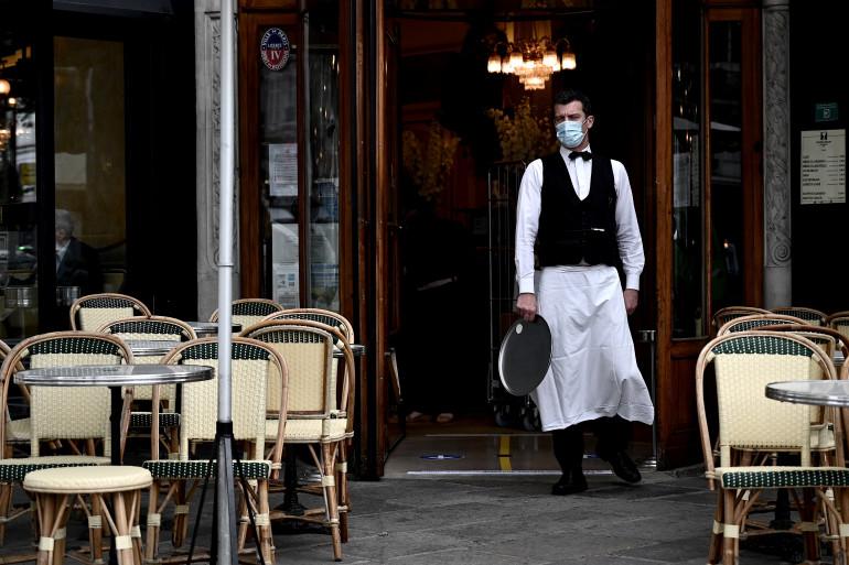Un serveur devant un café parisien durant la pandémie de nouveau coronavirus.