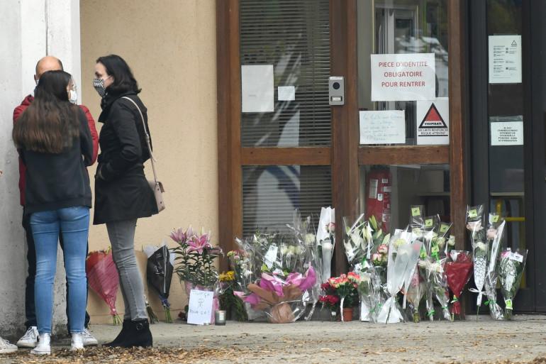 Des adultes et des enfants ont déposé des fleurs devant le collège du professeur assassiné à Conflans-Saint-Honorine.