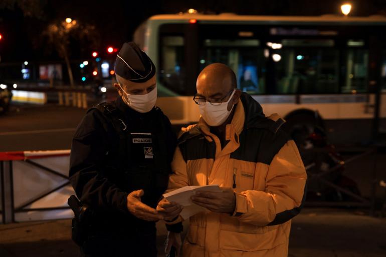 Un policier contrôle l'attestation dérogatoire d'un homme à Paris pendant le couvre-feu, le 17 octobre 2020