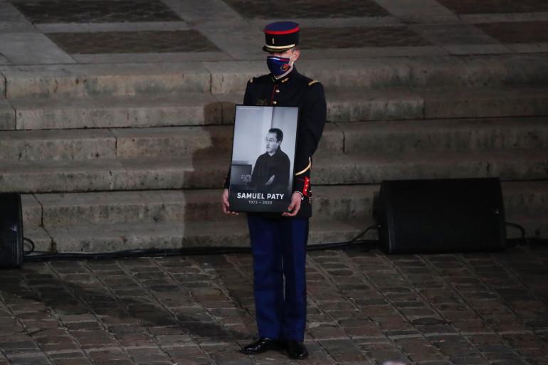 Un officier de la garde républicaine, avec le portrait de Samuel Paty