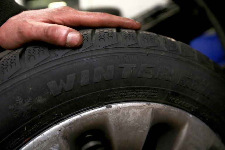 Un automobiliste tient un pneu hiver (illustration)