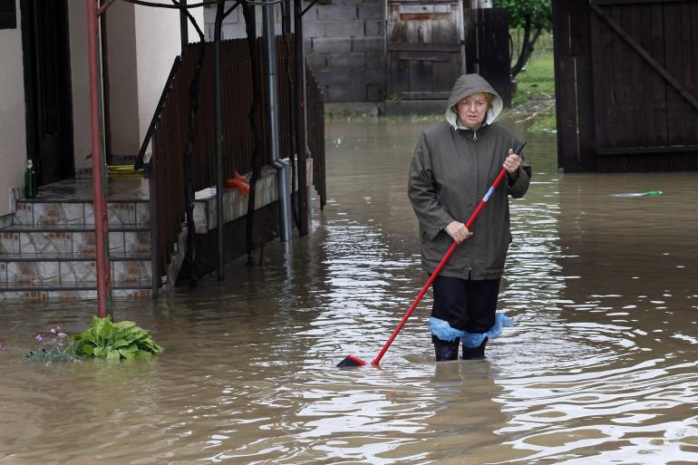 Un femme marche dans son jardin inondé, le 17 mai 2014 à Banja Luka, dans l'ouest de la Bosnie