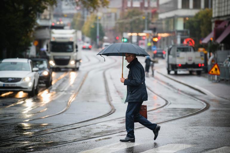 Un homme marchant sous la pluie à Stockholm (Suède) où aucun confinement n'est appliqué, le 22 octobre 2020.