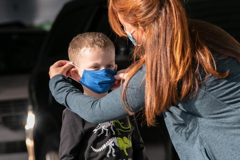 Une maman ajustant un masque sur le visage de son fils (illustration).