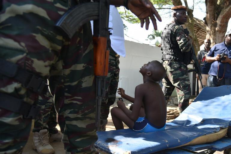 Un enfant entouré par des militaires à Grand Bassam après l'attaque qui a fait plusieurs morts en Côte d'Ivoire