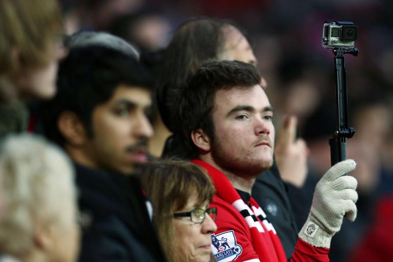 Un supporter de Manchester United filme un match de football avec une caméra GoPro (illustration).