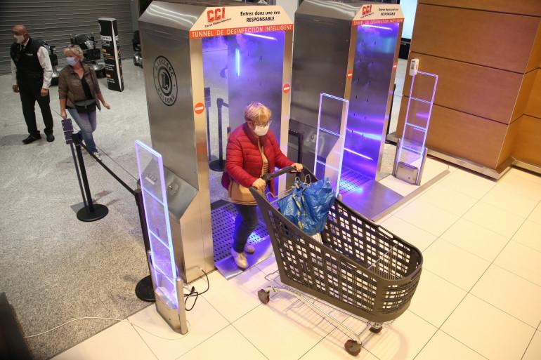 """Une femme marche dans un """"tunnel de désinfection"""" mis en place à l'entrée d'un supermarché d'Ajaccio le 9 novembre 2020."""