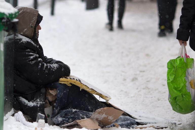Un sans-abri sur un trottoir enneigé de Paris