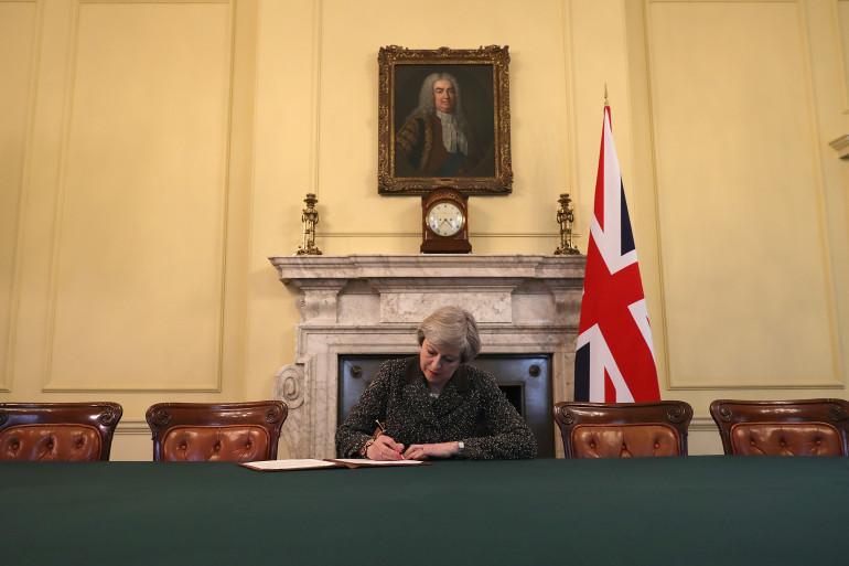 La Première ministre britannique Theresa May signe la lettre qui doit activer le Brexit, mardi 28 mars.