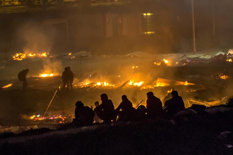 Des migrants devant le camp de Grande-Synthe réduit en cendres, le 11 avril 2017.