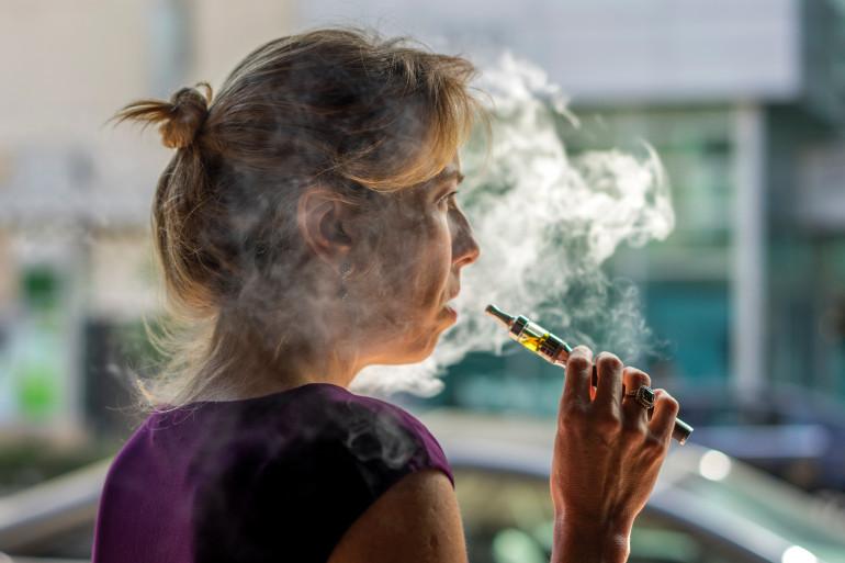 Une femme fume avec une cigarette électronique à Los Angeles en 2014.