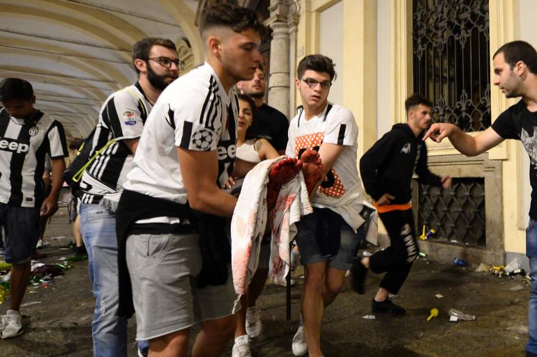Des supporters de la Juventus Turin transportent une femme blessée, samedi 3 juin 2017