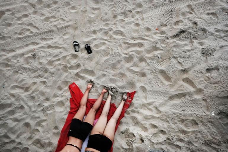 Deux femmes bronzant sur une plage (Illustration)