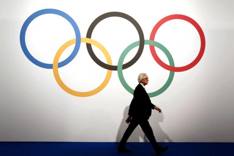 Un homme marche devant les anneaux olympiques (illustration)