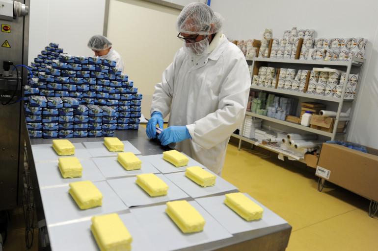 Un employé emballe des plaquettes de beurre (illustration)