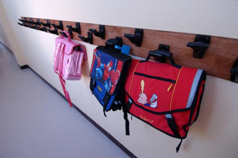 Des cartables accrochés dans un couloir d'école (photo d'illustration).