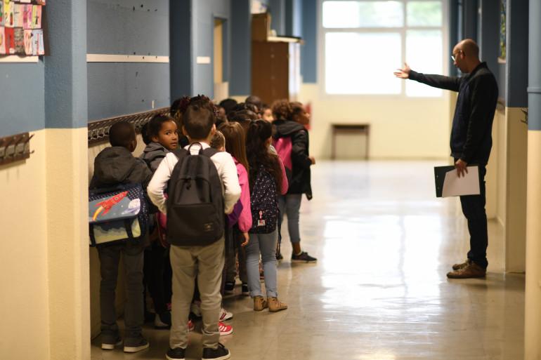 Des élèves en primaire dans le couloir avant de rentrer en classe