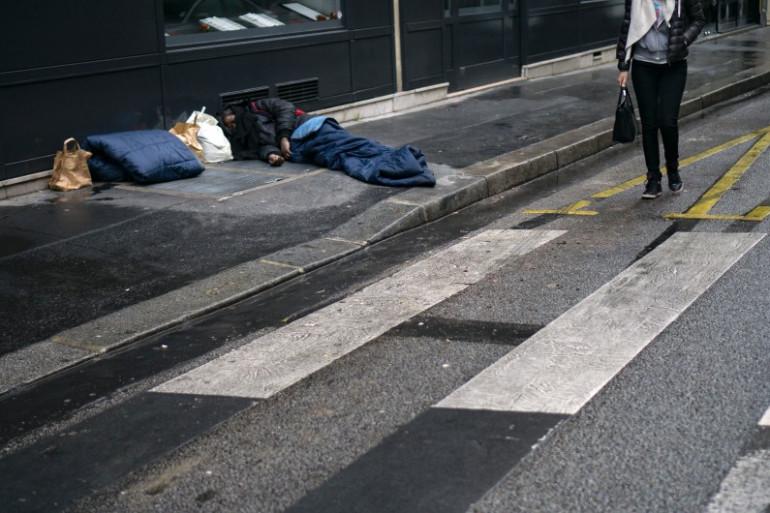 Une femme passe près d'un sans-abri à Paris, le 8 janvier 2017