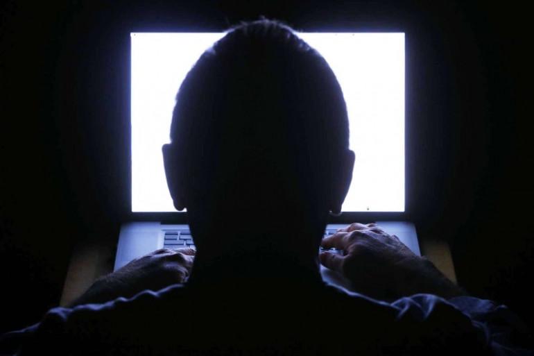 Une personne derrière un écran d'ordinateur
