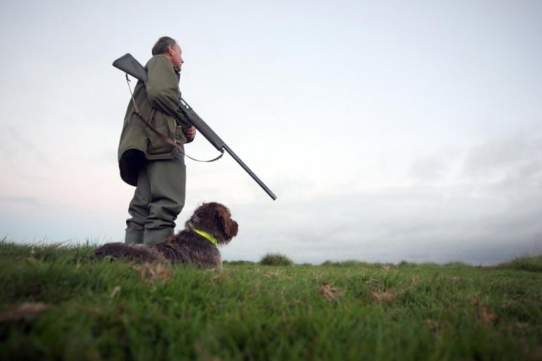Un chasseur patiente avec son chien (Illustration).