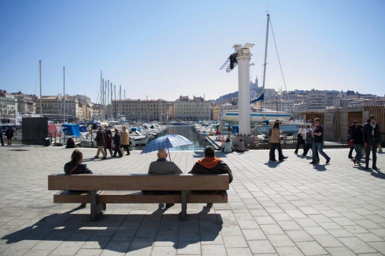 Des personnes profitent du soleil sur le Vieux Port de Marseille.
