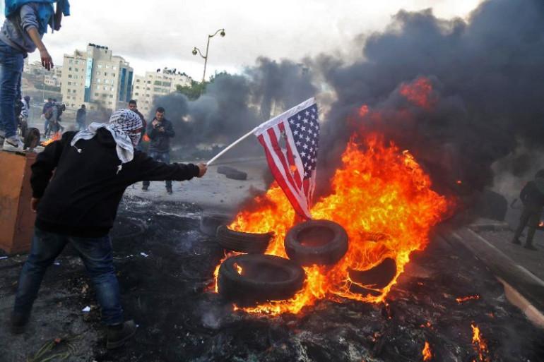 Un manifestant palestinien brûle un drapeau américain suite à la décision de Trump de reconnaître Jérusalem comme capitale d'Israël.