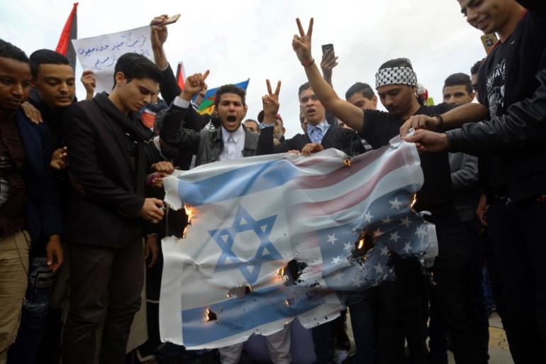 Des manifestants libyens et palestiniens brûlent une banderole portant le drapeau américain et israélien lors d'une manifestation, place des Martyrs à Tripoli le 8 décembre 2017.