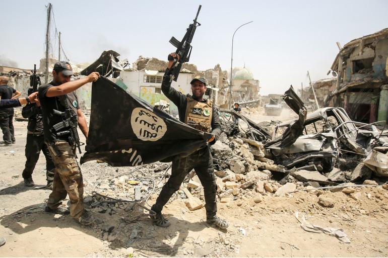 Des forces de l'antiterrorisme irakiennes brandissent un drapeau de Daesh à l'envers dans la vieille ville de Mossoul, le 2 juillet 2017