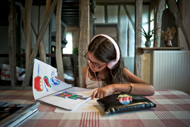 Une jeune fille écoutant de la musique au casque sur son lecteur MP3 (Illustration)