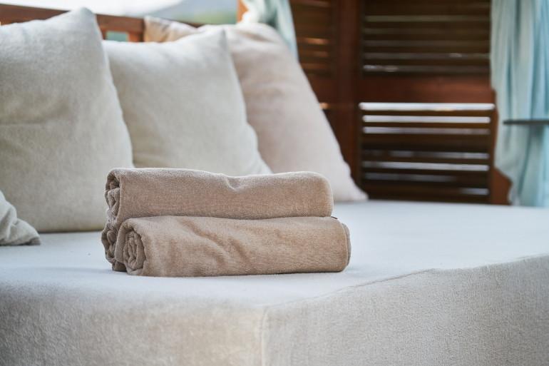 Des serviettes de bain déposées sur un lit d'hôtel (images d'illustration).
