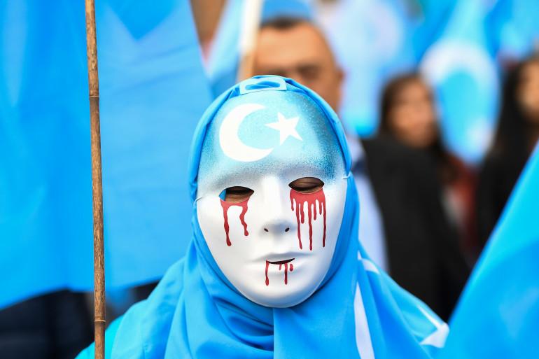 Un homme portant un masque avec des larmes de sang pour protester contre le sort réservé aux Ouïghours en Chine lors d'une manifestation en Belgique en 2018