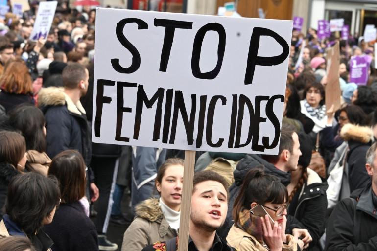 """Un manifestant brandit une pancarte """"Stop Féminicides"""" à la marche contre les violences faites aux femmes samedi 23 novembre 2020."""