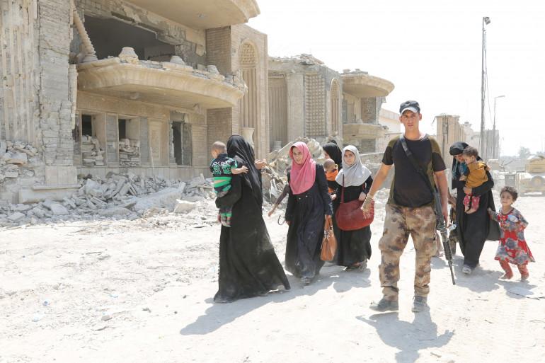 Un soldat irakien escorte des civils à Mossoul le 11 juillet 2017.