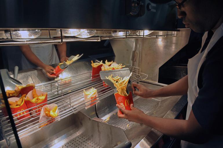 Un employé du restaurant McDonald's prépare une portion de frites (illustration)