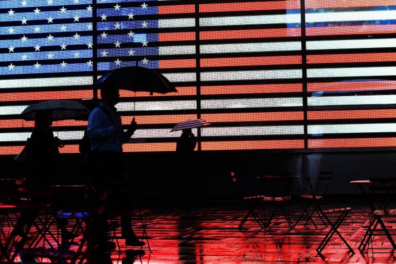 Des piétons passent devant les écrans de Times Square affichant un drapeau américain, le 6 novembre 2014 à New York (image d'illustration)