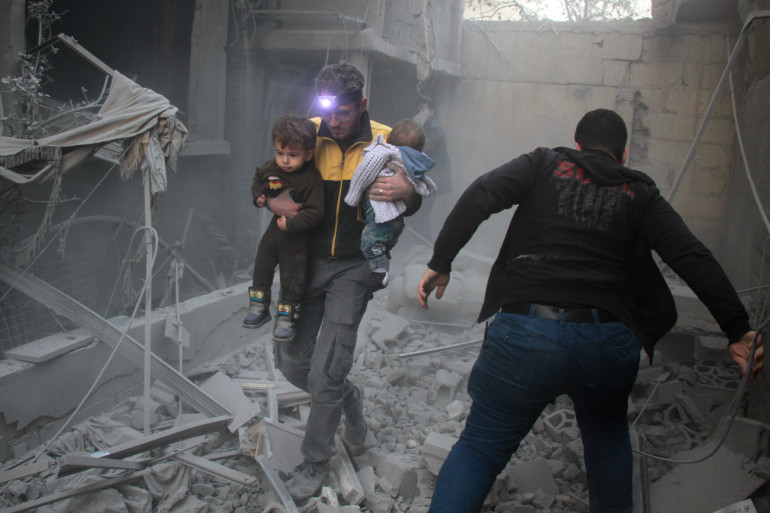 Un homme porte deux enfants après des bombardements à Douma, dans la région de la Ghouta en Syrie