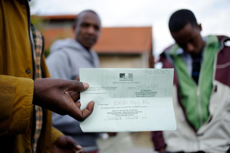 Un réfugié somalien montre son document officiel de demandeur d'asile le 22 octobre 2009 à Pontoise (archives)